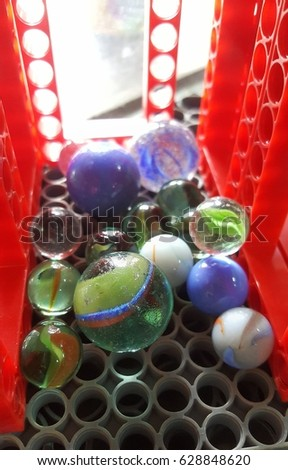 Colorful glass marble ball in plastic fram