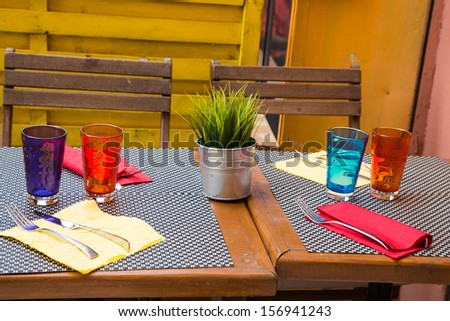 Colorful glasses and napkins on table with plant in patio
