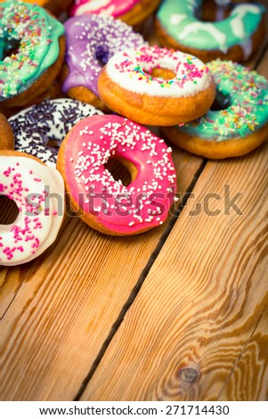 Colorful glazed donuts on the wooden table - stock photo