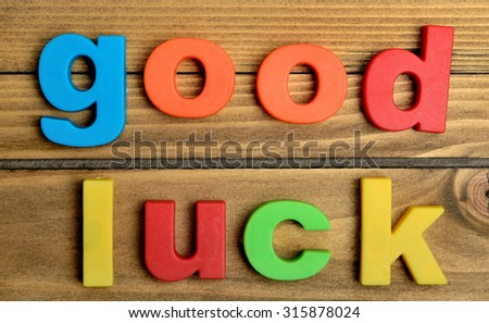 Colorful Good luck word on wooden table - stock photo