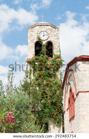 Colorful Greek Church with a clock tower  in the village of Pefkohori taken from a public road - stock photo