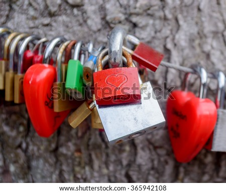 Colorful group of love locks padlocked to a cable symbolic of undying love between partners, a new trend amongst tourists considered vandalism by town authorities - stock photo