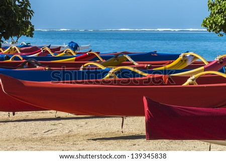 Colorful group of outrigger canoes at the shore
