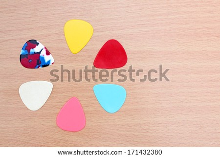 colorful guitar picks on laminate wood for background