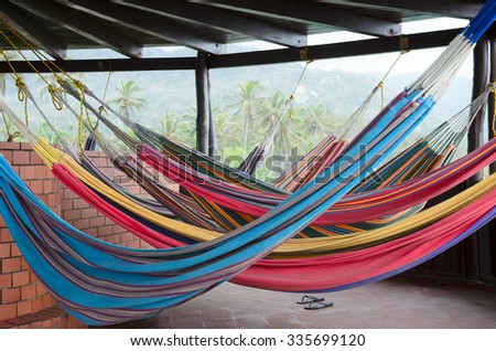 Colorful hammocks hanging under the roof in tropical paradise