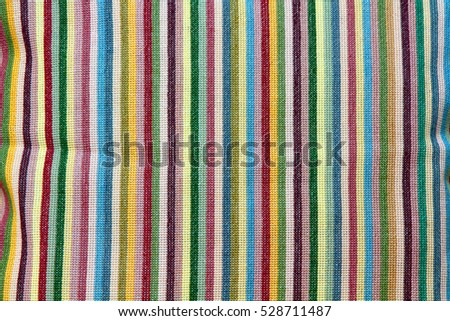 Colorful hand-embroidered striped pattern on pillow.