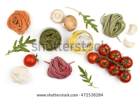 Colorful hand-made pasta and ingredients: vegetables and oil, top view. Italian healthy food cooking.