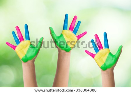 Colorful hand of the child isolated on bokeh background - stock photo
