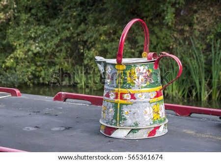 Colorful hand painted water can on top barge