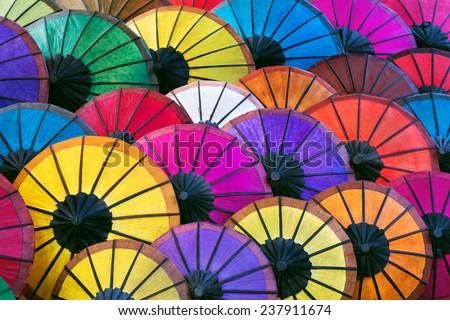 Colorful handmade Asian umbrellas on display at night market in Luang Prabang, Laos. - stock photo