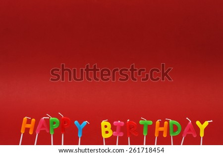 Colorful happy birthday candles on red background - stock photo