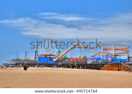 Colorful HDR image of a ferris wheel and other rides and attractions in partially cloudy sky at the Santa Monica amusement Pier, CA, USA, 2016 - stock photo