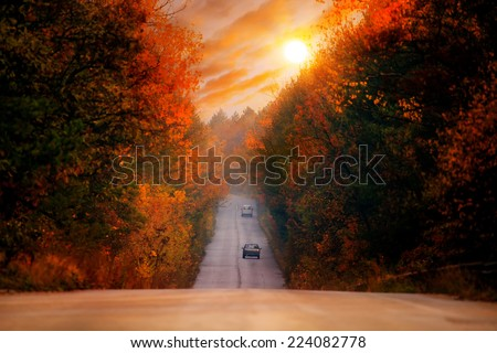 colorful HDR red sunset over the straight high mountain autumn road  - stock photo