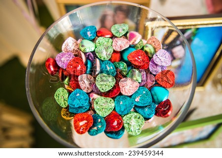 Colorful heart shaped chocolate in a wine glass - stock photo
