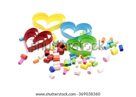 Colorful heart-shaped paper crafts, quilling with small colorful rolls of paper on white background for Valentine's day or love concept