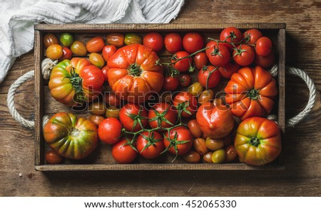 Colorful Heirloom tomatoes in rustic wooden tray over dark wooden background, top view, horizontal composition - stock photo