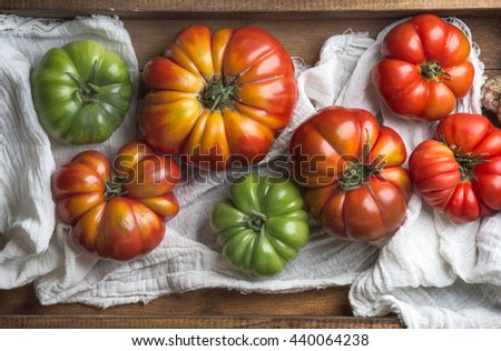 Colorful Heirloom tomatoes in rustic wooden tray, top view - stock photo