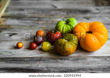 Colorful heirloom tomatoes on rustic wooden background - stock photo