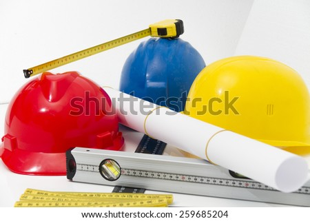 Colorful helmets and tools for construction drawings and buildings - stock photo