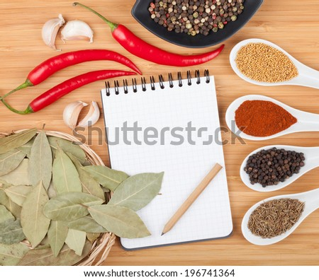 Colorful herbs and spices selection. Aromatic ingredients on cutting board with blank notepad copyspace - stock photo