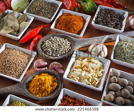 Colorful herbs and spices selection. Aromatic ingredients on wood table - stock photo