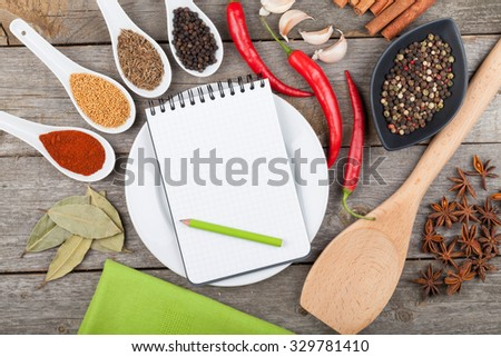 Colorful herbs and spices selection. Aromatic ingredients on wood table with blank notepad copyspace - stock photo