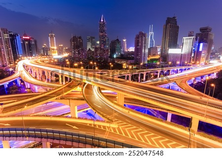 colorful highway overpass and modern city skyline at night - stock photo