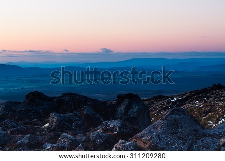 Colorful hills and rocks west of lake Taupo, New Zealand. A stunning evening scene across a dramatic landscape. - stock photo