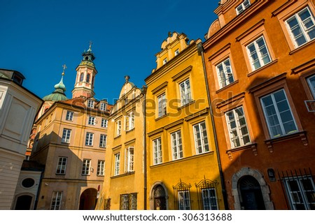 Colorful historical buildings facade in the Warsaw's old town on the morning sunlight. View from below - stock photo