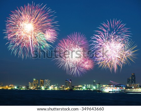 Colorful holiday fireworks in the night sky with boat floating on the sea and the city in background - stock photo