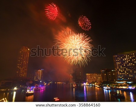 Colorful holiday fireworks in the night sky with city in background