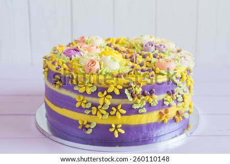 Colorful homemade cake decorated with cream flowers - stock photo