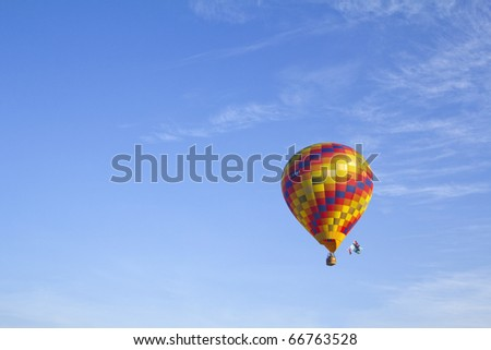 Colorful hot air balloon against a blue sky - stock photo