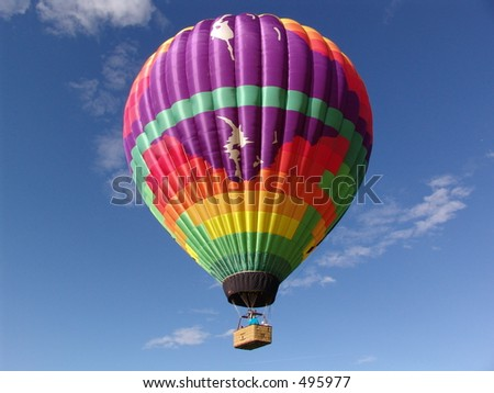 Colorful hot air balloon and basket, rising in the blue sky