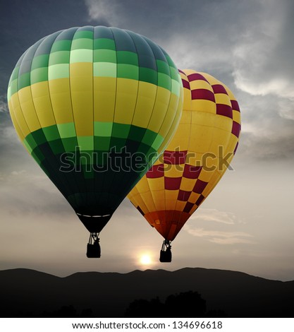 Colorful hot air balloon floating across a surreal golden sunset skyline. - stock photo