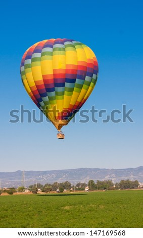 Colorful Hot Air Balloon flying above Fields - stock photo