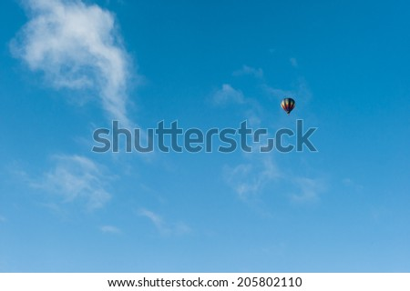 Colorful hot air balloon flying high in a blue sky. Fun and happiness. A relaxing and cheerful ballooning experience.