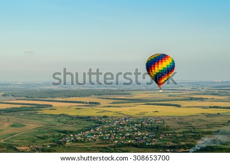 Colorful hot air balloon flying over the village, forest and fields - stock photo