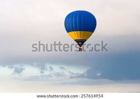 Colorful hot air balloon in blue sky. Blue and yellow aerostat - stock photo