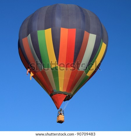 Colorful hot air balloon isolated against blue sky