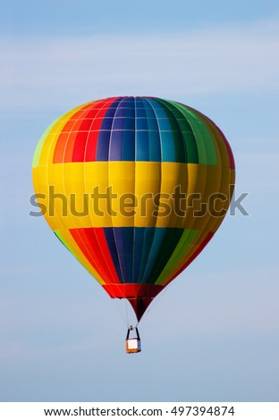 Colorful hot air balloon moving up in the blue sky.