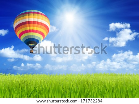 Colorful hot air balloon over green field with sun beam background - stock photo