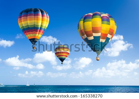 Colorful hot air balloon over the ocean with blue sky background - stock photo