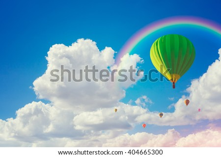colorful hot air balloons and rainbow with cloudy blue sky background - stock photo