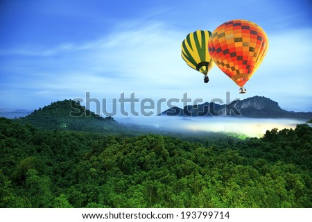 Colorful hot-air balloons flying over the mountain - stock photo