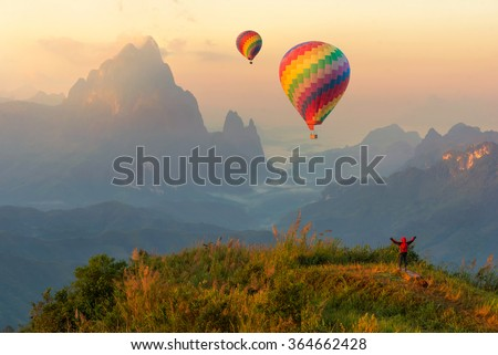Colorful hot-air balloons flying over the mountain and traveler,travel concept - stock photo