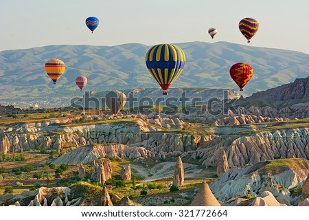 Colorful hot air balloons flying over the valley at Cappadocia, Anatolia, Turkey. Volcanic mountains in Goreme national park. - stock photo