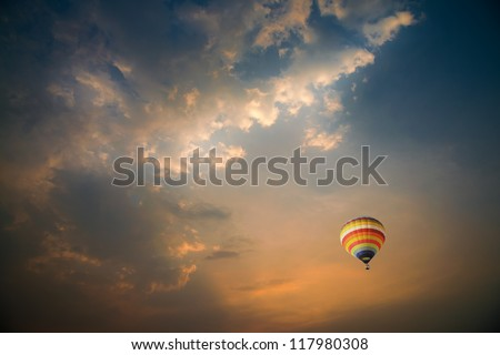Colorful hot air balloons over the dramatic sky during sunset - stock photo