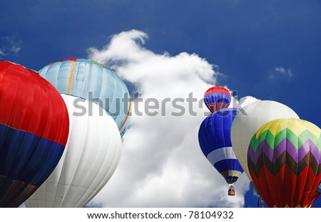 Colorful hot air balloons ready to take off on a beautiful blue sky with copyspace for text. - stock photo