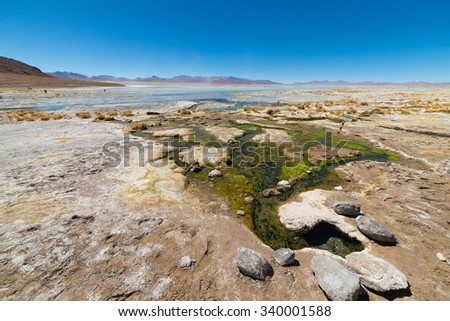 Colorful hot spring with deposits of minerals and algae on the Andean Highlands, Bolivia. Salt lake, mountain range and volcanos in the background on the way to the famous Uyuni Salt Flat. Wide angle. - stock photo